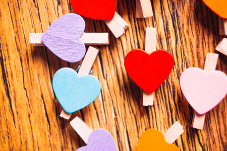 colorful  clothespins with little hearts on wooden background close up
