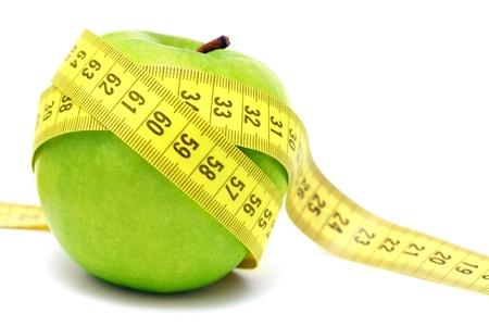 metro medir: Manzana verde y cinta métrica aisladas sobre fondo blanco