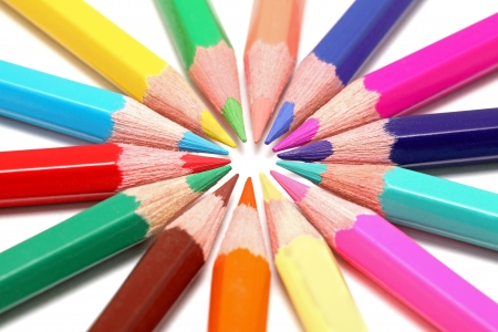 Circle of colored pencils isolated on white background with shadows