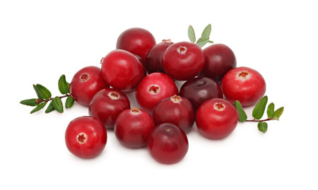 Pile of ripe cranberries with green leaves isolated on white background