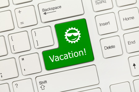 Close-up view on white conceptual keyboard - Vacation (green key)