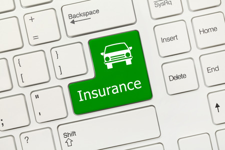 Close up view on white conceptual keyboard - Insurance (green key with car icon) photo