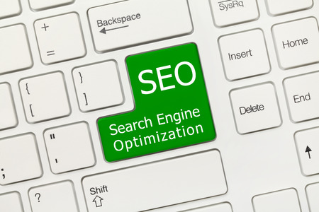 Close-up view on white conceptual keyboard - SEO (green key) photo