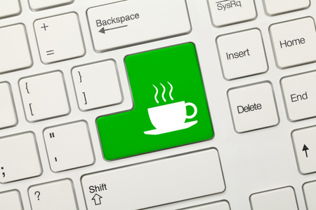 Close-up view on white conceptual keyboard - Coffee cup (green key) photo