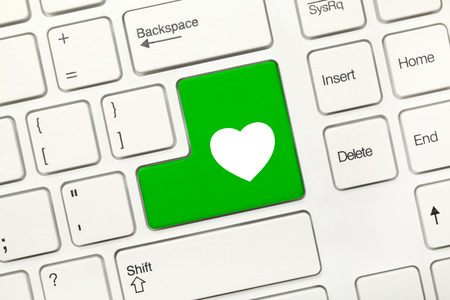 Close-up view on white conceptual keyboard - Green key with heart symbol photo
