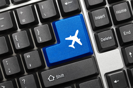 Close-up view on conceptual keyboard - Blue key with airplane symbol photo