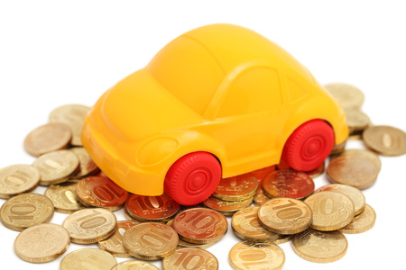 accumulate: Toy auto and pile of golden coins isolated on white background Stock Photo