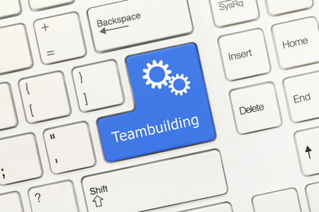 teambuilding: Close-up view on white conceptual keyboard - Teambuilding (blue key with gear symbol) Stock Photo
