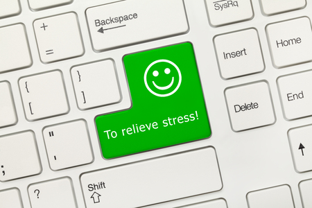 Close-up view on white conceptual keyboard - To relieve stress (green key)