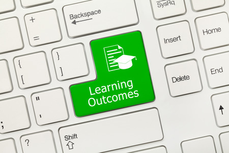 Close-up view on white conceptual keyboard - Learning Outcomes (green key)
