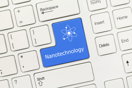 Close-up view on white conceptual keyboard - Nanotechnology (blue key with Nuclear symbol)