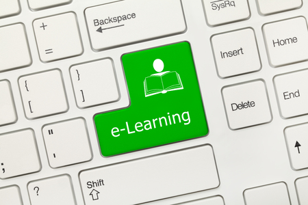 Close-up view on white conceptual keyboard - e-Learning (green key with man and book symbol) Stockfoto
