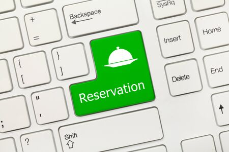 Close-up view on white conceptual keyboard - Reservation (green key with dish symbol)