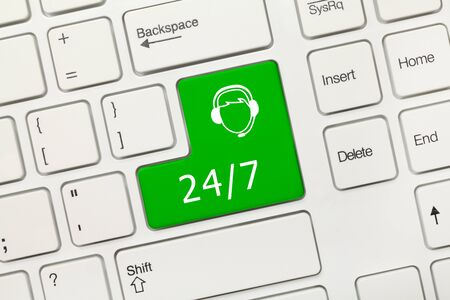 Close-up view on white conceptual keyboard - 24/7 (green key with operator symbol)