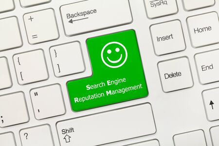 Close-up view on white conceptual keyboard - Search Engine Reputation Management (green key)
