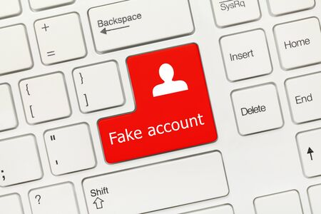 Close-up view on white conceptual keyboard - Fake account (red key) Stock Photo