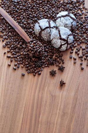 Spread on a wooden table coffee beans with spices with three cakes. With a wooden spoon. Great background for cafe menu design.