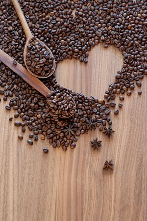 Coffee beans spilled on a heart-shaped wooden table with spices with two wooden spoons. Great background for cafe menu design.