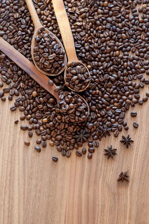 Coffee beans spilled on a wooden table with spices with three wooden spoons. Great background for cafe menu design.