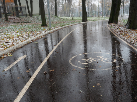 ciclovia: Sign on a wet bicycle path after the thawed snow in the fall