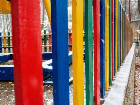 Multi-colored protection of the playground in the park in the fall.