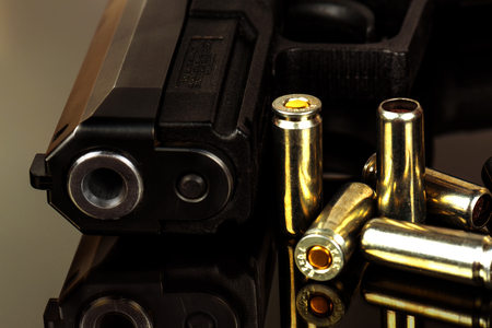 The black gun and cartridges to him on a black background close up.