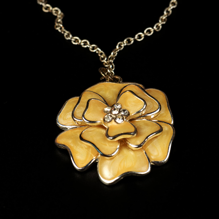 Yellow pendent in the form of a flower, costume jewelry, close up on a black background. Stock Photo