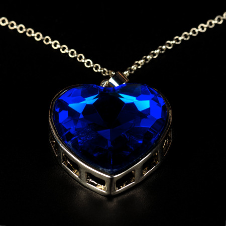 Blue pendent in the form of heart, costume jewelry, close up on a black background.