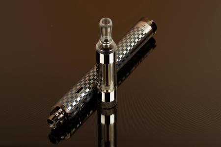 coil: Cigarrillo electrónico (vape) en el aspecto clasificado contra un fondo oscuro. Foto de archivo