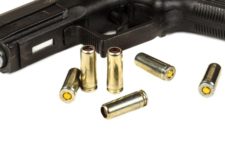 gunfire: The black gun and cartridges to him on a white background close up.