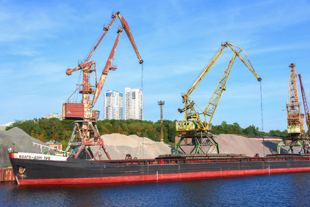 Russia, Moscow August 2018: Unloading of the barge with crushed stone port cranes in the port.