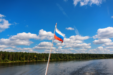 Russian flag flies on the flagpole against the sky. Freedom is independence and patriotism.