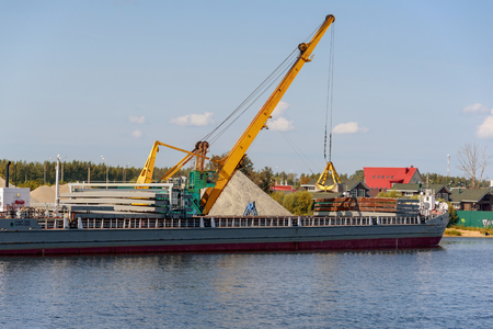 Loading barge with sand and rubble on a small berth. Freight transport logistics. Russia, Moscow region, August 2108.