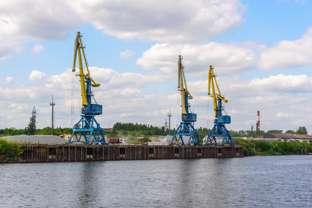 Russia, Moscow August 2018: Unloading of the barge with crushed stone port cranes in the port. Imagens - 124871925