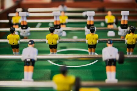 Table football, table football with close-ups of yellow and white players.