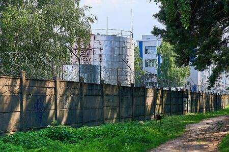 The factory building is fenced with a concrete fence. Protection and security of the external perimeter of the territory.