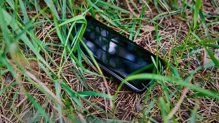 A lost mobile phone lies on the grass close-up. Phone loss. Stock Photo
