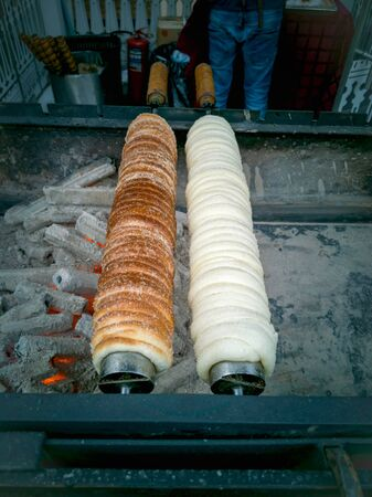 Cooking Grilled Trdelnik at a point of sale. National Czech street food.