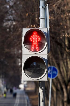 A red signal on the traffic light for pedestrians. Pedestrian traffic is prohibited. Imagens