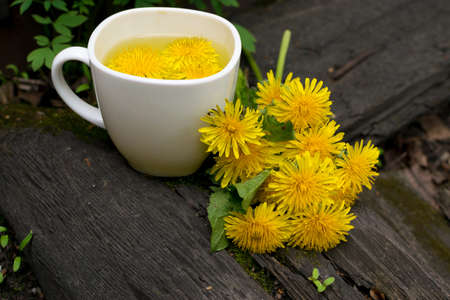 Dandelion flower tea infusion in white cup close up. Herbal beverage, yellow flowers and leaves tisane on natural dark background Banco de Imagens