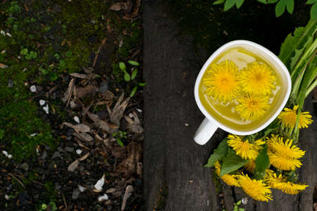 Dandelion flower tea infusion in white cup close up. Herbal beverage, yellow flowers and leaves tisane on natural dark background Banque d'images