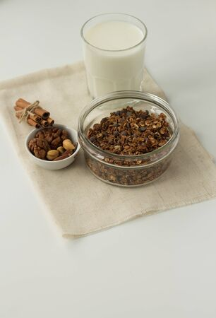 homemade baked muesli and milk on white background, top view.