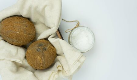 Fresh coconut oil on a white table, coconuts in a basket Stock Photo