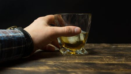Man's hand holding Glass of whiskey with ice cubes on rustic wooden table with copy-space Stockfoto