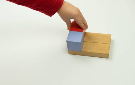 Hand sets a wooden cube isolated on a white background.