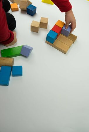 Hand sets a wooden cube. It is isolated on a white background. the child plays with wooden kibiks