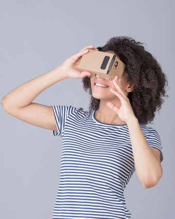 simulator: Girl using virtual reality device cardboard vr over gray background