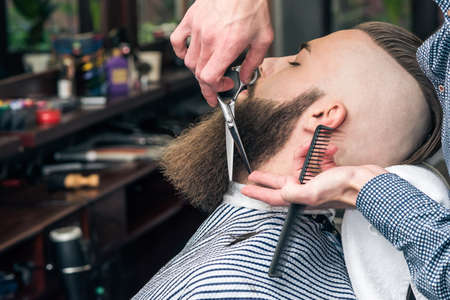 barbershop: Handsome man with undercut in barbershop. Mustache styling by a professional barber.