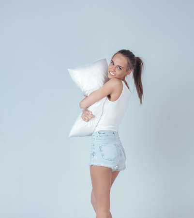 nice smile: Beautiful girl with a nice smile posing with a pillow over gray background Stock Photo