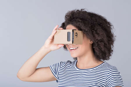 simulator: Smiling girl using virtual reality device cardboard vr over gray background Stock Photo
